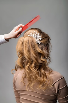 Wave curls hairstyle. hairdresser making hairstyle to blond hair woman with long hair using comb on gray background.