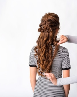 Wave curls hairstyle. hairdresser making hairstyle to red brown hair woman with long hair on white background