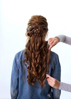 ウェーブカールヘアスタイル。くしを使って長い髪の赤茶色の髪の女性に髪型を作る美容師