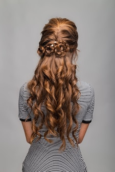 Wave curls hairstyle. hairstyle on red brown hair woman with long hair on gray background.