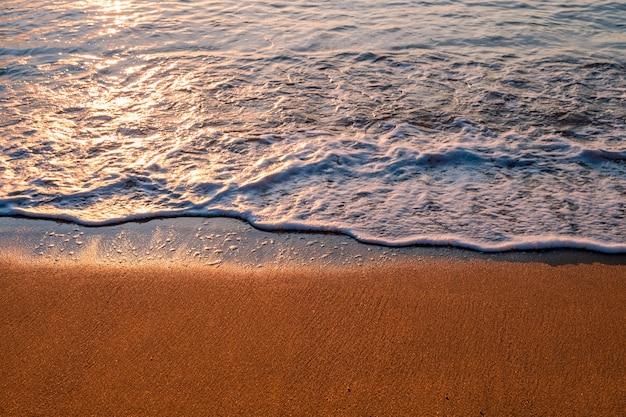 일출 해변에서 파도 거품과 푸른 바다.