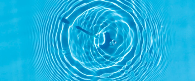 Wave from a drop of water on blue water under natural light. top view, flat lay.