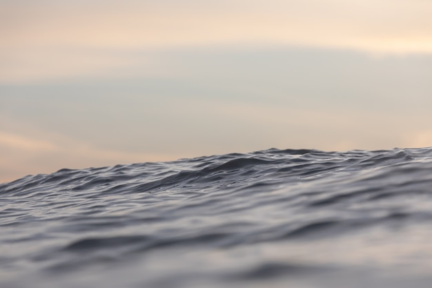 日の出または日の入りの海の波