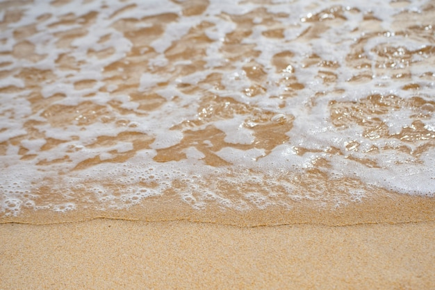 Wave of  ocean on sandy beach background.