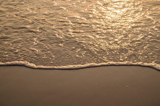 Волна на золотом песке утром