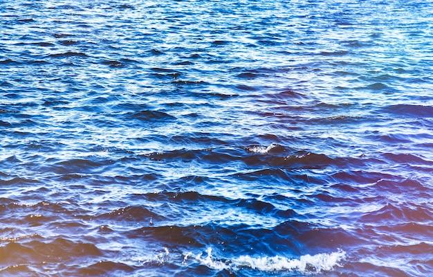 Волновой узор на поверхности пресного или морского водоема. обои фон плещущихся речных волн на морской поверхности воды или океанских волн. фон природа обои концепция. на фото озеро рябь. копировать пространство