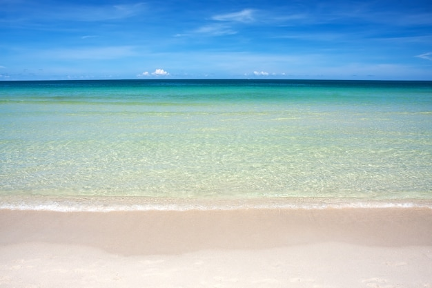 Wave of the sea on the sand beach against blue sky