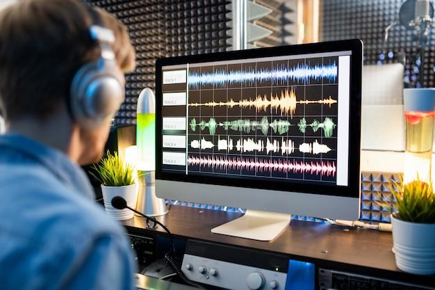 コンピューター画面上の波形サウンドの視覚化とスタジオ内の前に座っている現代のディージェイまたはオーディオエディター