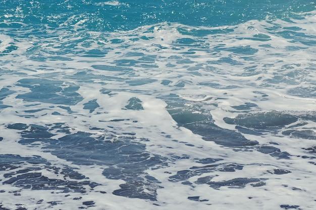 Волны и пены на пляже крупным планом.