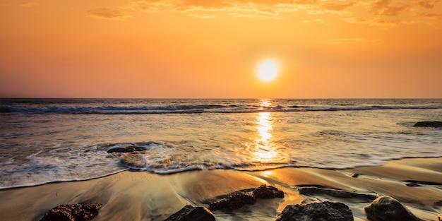 파도 일몰 해변에 바위