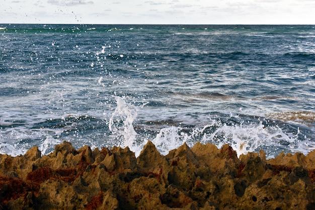 Волны ударяются о скалы. атлантический океан