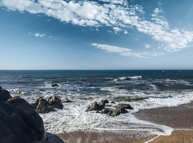 ポルトガルの風の強い日に岩の多いビーチに到着する波
