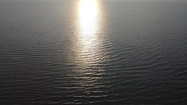 海の波と水中の朝日の輝き。航空写真。