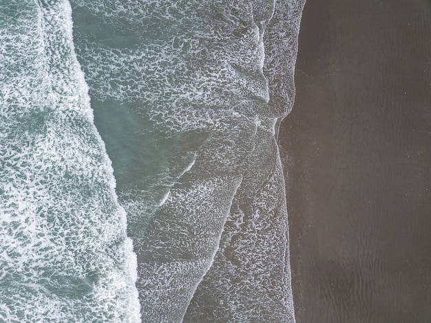 Waves and beach aerial shot from bird eye view made in christchurch new zealand