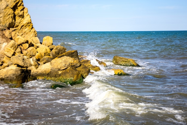 Waves beat against stones on a sunny day