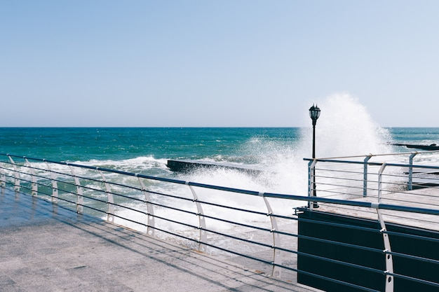 Waves break on the pier on a sunny day