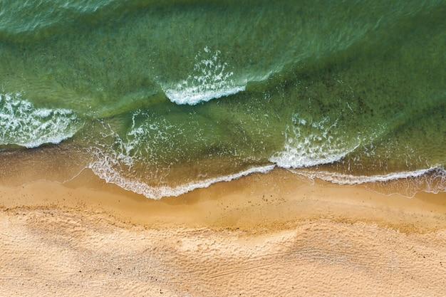 ビーチの砂に砕ける波