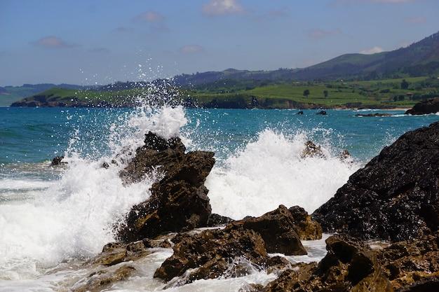 Onde che si infrangono sulle rocce con un oceano blu dietro di loro