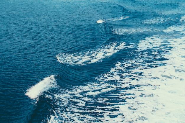 Волны заделывают выстрел. синяя очаровательная морская вода. гипнотизирующие волны креста. воды эгейского моря. волны выходят на море на кораблях.