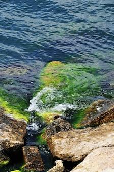 파도가 돌 해안에 부서집니다. 배경, 질감입니다. 파도, 돌, 해변.