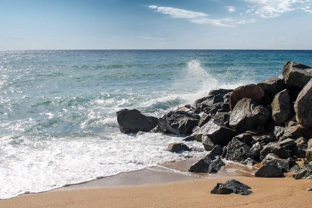 プエルトリコの晴れた日にビーチの岩に打ち寄せる波