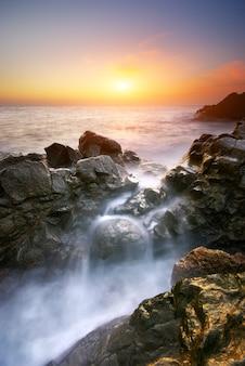 Волны разбиваются о берег во время заката