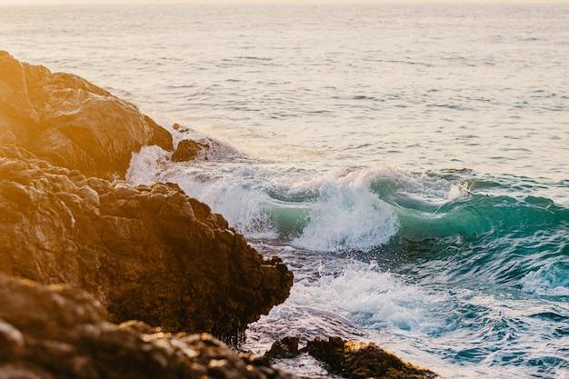 日の出の間に岩に衝突する波