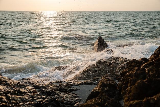 Waves crashing on rock cliffs at sunrise khao laem ya national park, rayong, thailand