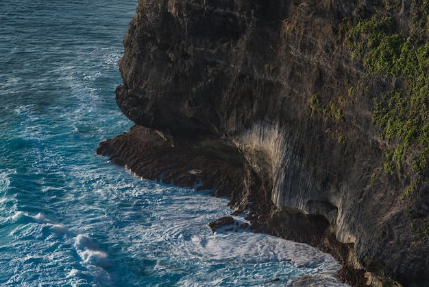 Waves hit the rock. famous uluwatu temple in bali, indonesia.