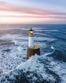 Waves hitting a lighthouse in scotland