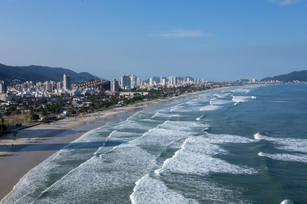 Волны ударяя пляж на фоне города