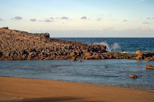 プエルトリコのビーチの粘土質の岩層に影響を与える波