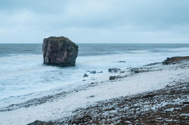 Волны в движении, мягкий фокус. из моря выступает большая скала. шторм на берегу белого моря. волны с белой пеной катятся по каменистому берегу. полярный дикий пейзаж.