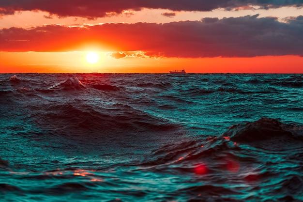 Волны в океане на фоне жаркого и романтического заката