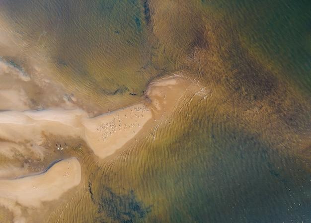 Волны на желтом песчаном пляже побережья океана, вид с высоты