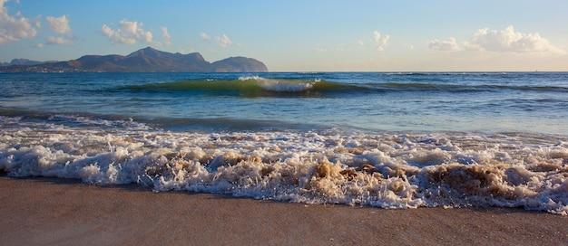 Волны, лежащие на песке во время заката