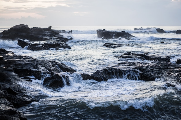 The waves of the ocean are breaking against the rocks. splashing ocean waves at sunset.