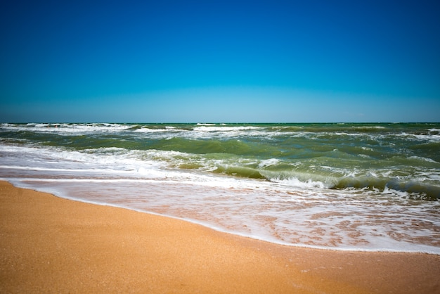 화창한 따뜻한 여름 날에 모래 해변에 튀는 푸른 물과 시끄러운 바다의 파도. 바다와 낙원에서 휴가 개념. copyspace