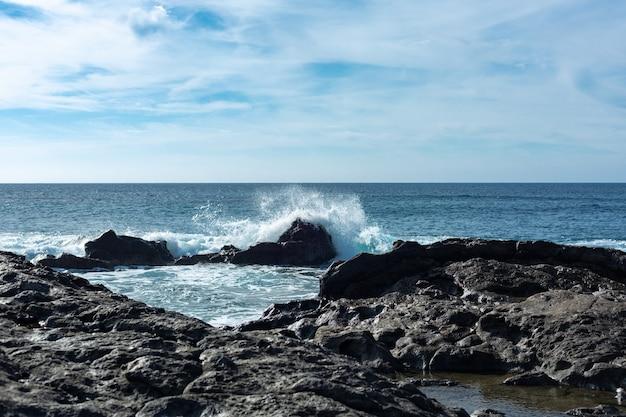 スペインのランサローテ島の冷やされた溶岩の周りに大西洋の波が飛び散っています。
