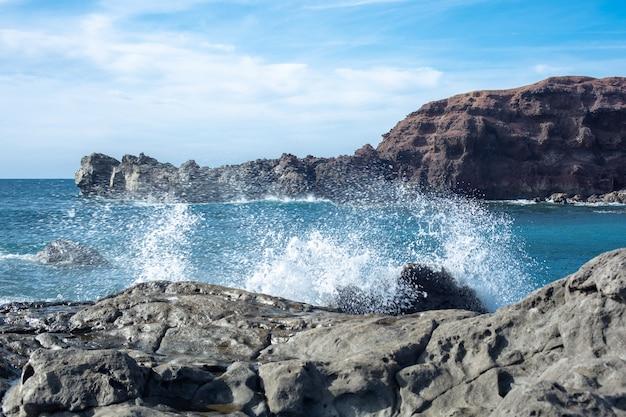대서양의 파도가 스페인 란 사로 테 섬의 냉각 된 용암 주위로 튀고 있습니다.