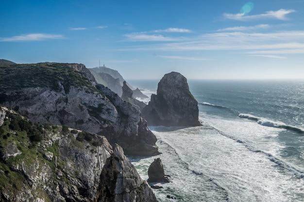 青空の下で岩の多い海岸線に打ち寄せる海の波