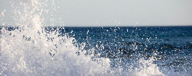 Волны плескались в очень ветреный день на закате синего моря
