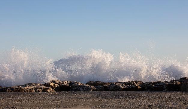 Волны плескались о скалы в очень ветреный день на закате