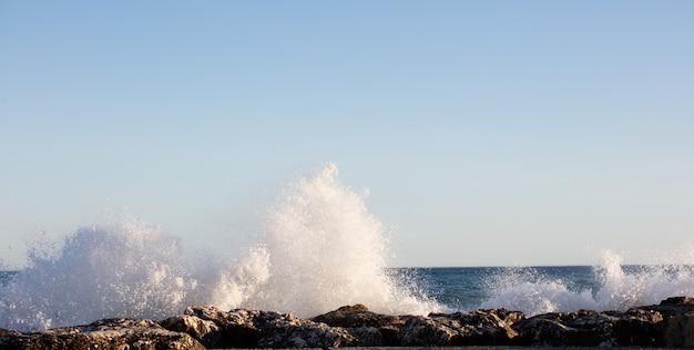 Волны плескались по скалам в очень ветреный день на закате