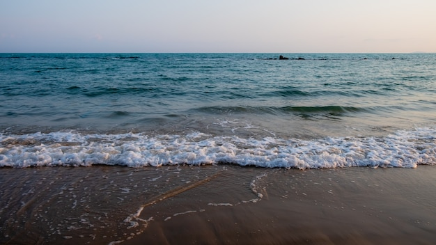 Waves wash over dark sand on the beach
