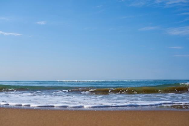 地平線を越えて行く地中海の砂浜の泡の波