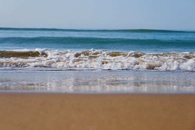 Волны с пеной на песчаном пляже средиземного моря уходят за горизонт