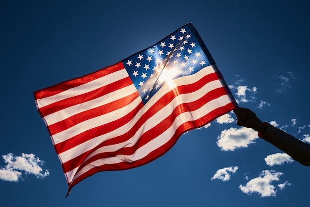 Развевающийся флаг америки на открытом воздухе рука держит национальный флаг сша на фоне голубого облачного неба день независимости сша символ американского патриотизма