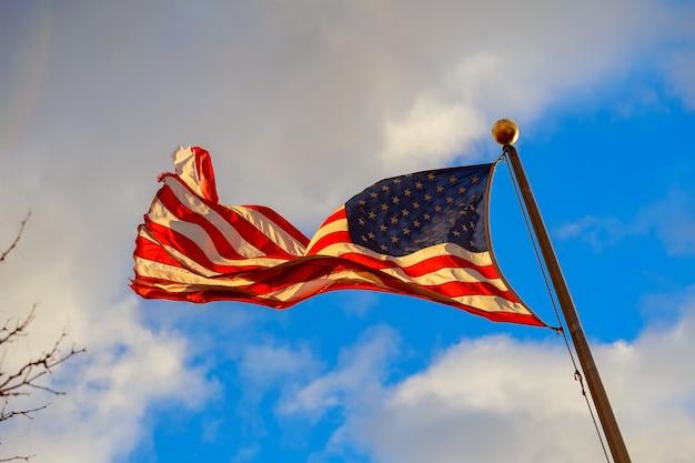 Размахивая американский флаг на фоне голубого неба.