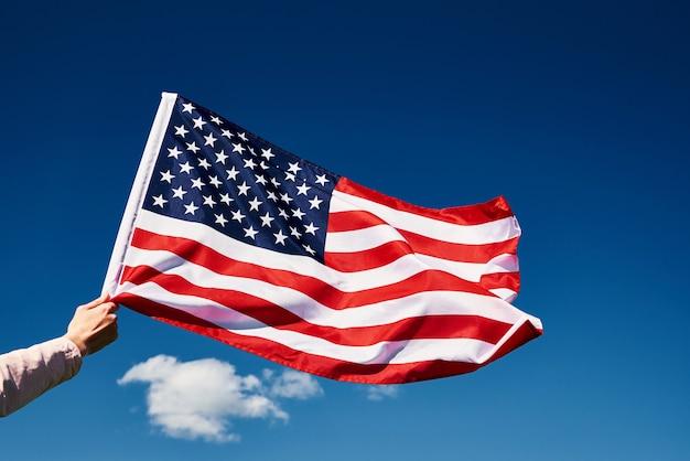 Развевающийся американский флаг на открытом воздухе рука держит национальный флаг сша на фоне голубого облачного неба день независимости 1 июля